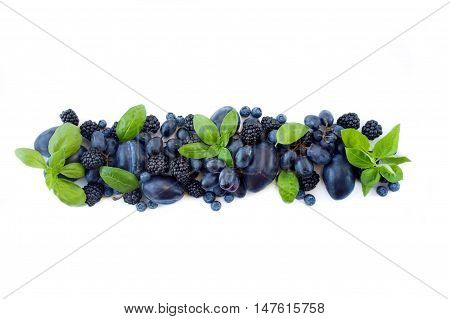Group of fresh fruits and berries with basil's on a white background. Ripe blueberries, grapes, plums and blackberries. Top view with copy space.