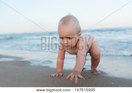 Baby blond girl crawling on a sandy beach