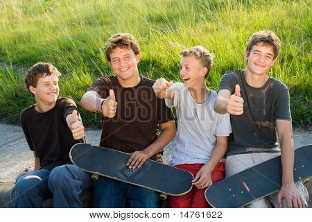group of teen boys resting on playground after playing skateboard