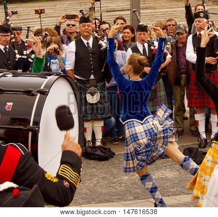 MOSCOW, RUSSIA - September 4, 2016: Girl dancing during a performance of Celtic pipes and drums band surrounded by townspeople in the Park of arts