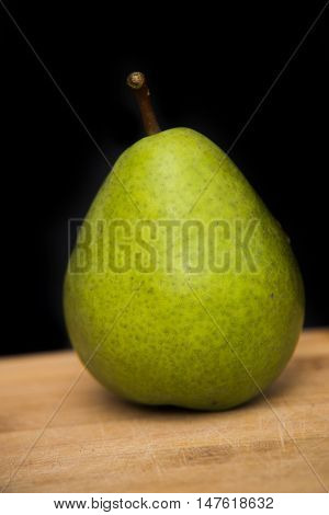 Close Up On Pear On Wood With Black Background