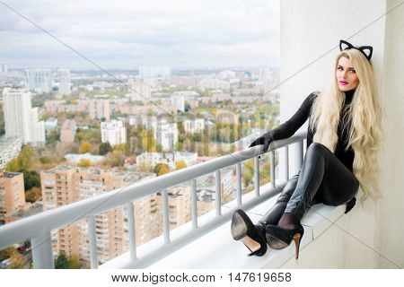 Beautiful sexy woman in latex cats costume is sitting on balcony in city