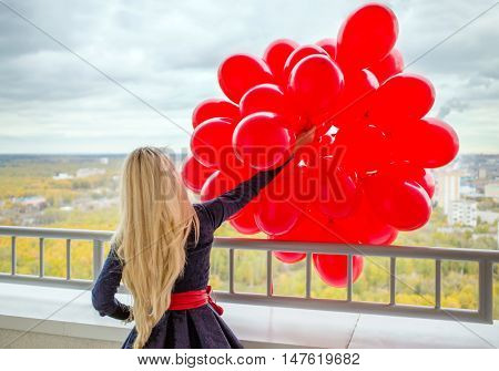 Young woman with long blond hair holds red balloons at balcony, back view
