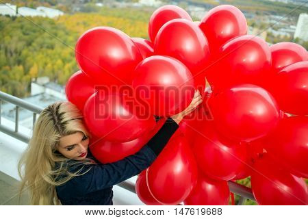 Young woman with long blond hair holds red balloons at balcony, top view