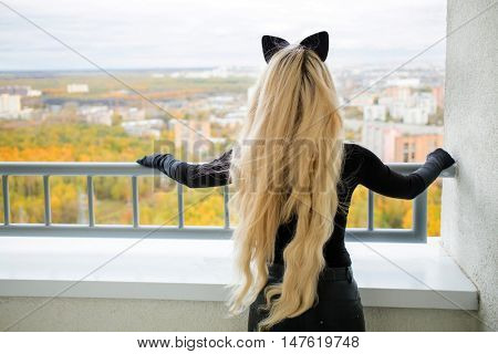 Beauty woman with long blond hair and cats ears is standing on balcony, back view