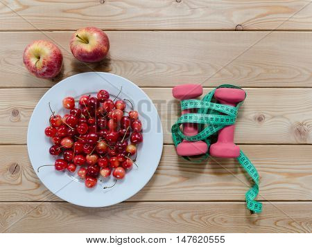Diet concept. cherries on plate red apples dumbbells and measuring tape on wooden table