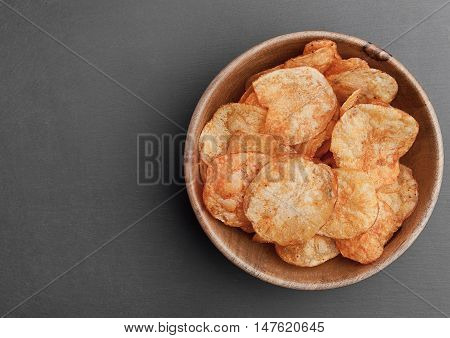 Bowl with potato crisps chips on black stone board. Junk food