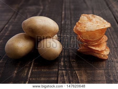 Fresh potatoes and crisps healthy and junk food on wooden board