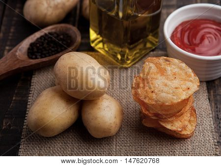 Fresh potatoes and crisps with pepper and sause on wooden board.