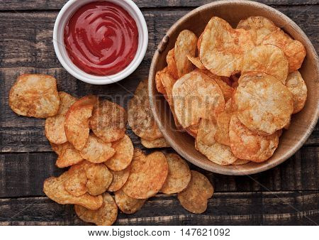 Bowl with potato crisps chips and ketchup on wooden board. Junk food