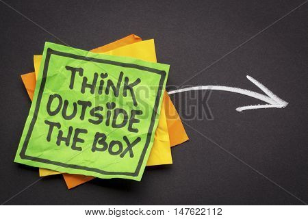 think outside the box - reminder note against black paper with white chalk drawing