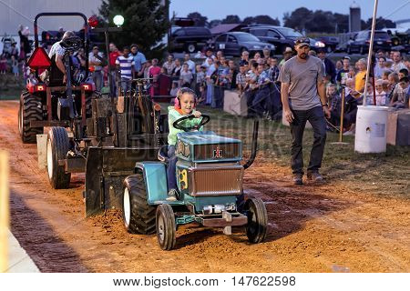 MYERSTOWN PENNSYLVANIA - SEPTEMBER 16 2016: A young girl drives a modified lawn tractor at Myerstown East End Days. The tractor pull is an annual community event.