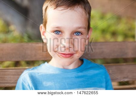 boy soiled in chocolate ice cream. impish boy sitting on a park bench with ice cream. looking at camera. Closeup
