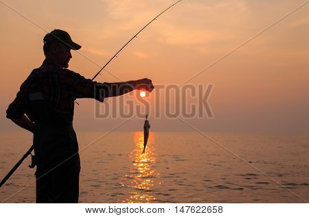 fisherman caught a fish at sunset. silhouette of a fisherman with a fishing rod and a caught fish. fishing with spinning, fly fishing. empty space for your text