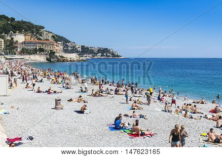 NICE FRANCE - JUNE 22 2016: Crowded municipal beach near Promenade des Anglais in City of Nice Cote D'azur Mediterranean sea France