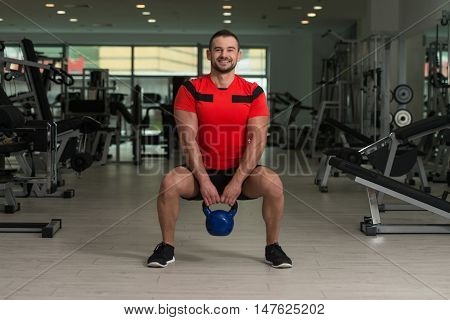 Fitness Instructor Exercising With Kettle-bell