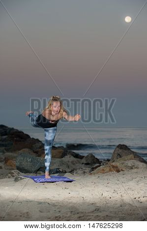 Portrait view of female athlete practicing Balancing Stick Pose under full Harvest Moon.