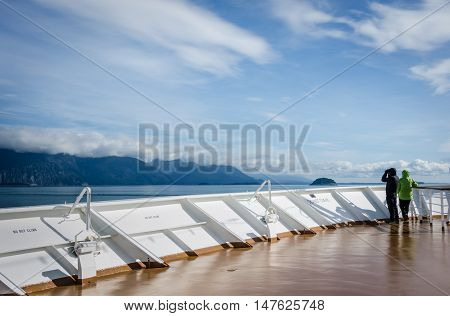 GLACIER BAY - ALASKA SEPTEMBER 11, 2016: Cruise ship passengers look out for marine life while sailing in Glacier Bay National Park and Preserve in Southeast Alaska.