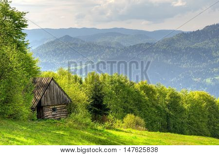 Spring mountain landscape. Wooden hut in a clearing in the mountains.