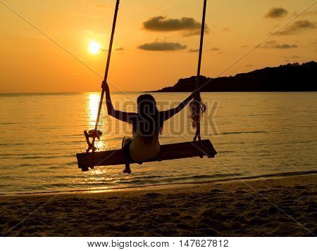 Silhouette of woman playing rope swing that hang over beach at sunset. Concept of relax enjoy joyful in summer.