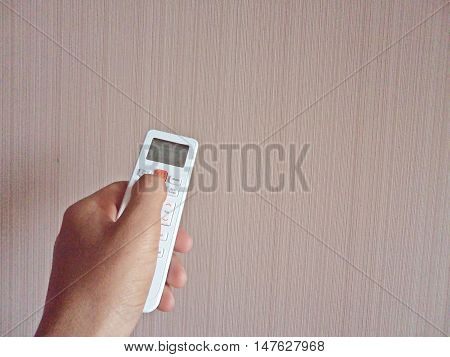 Remote control in hand for electric devices on wall background