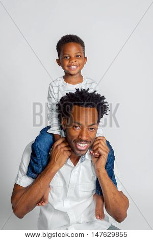 A young African American boy sits atop the Shoulders of his Dad.