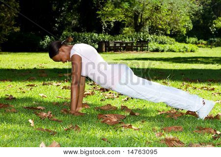 young african american woman doing push-ups in park