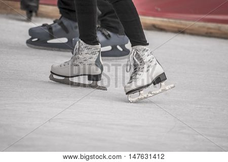 Young woman skating on ice. Ice skates as a detail SELECTIVE FOCUS
