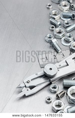 Proportional Divider, Ruler, Screws And Bolts On Metallic Scratched Background