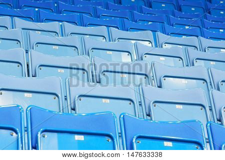 Rows of blue empty seats with numbers in big modern sport stadium