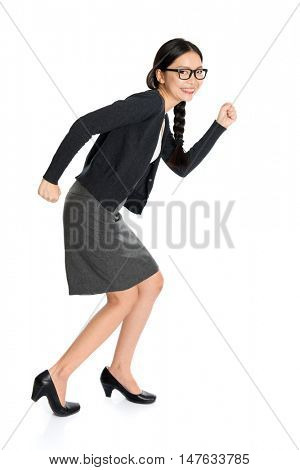 Full length portrait of young Asian girl running, isolated on white background.