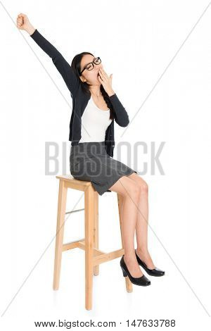 Full body portrait of young Asian woman yawning, sitting on high chair, isolated on white background.