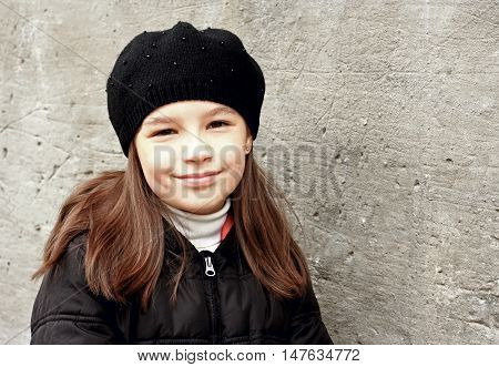 Little smiling girl stands against backdrop of the old wall
