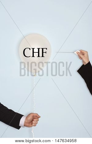 Cropped hands holding needle and popping balloon