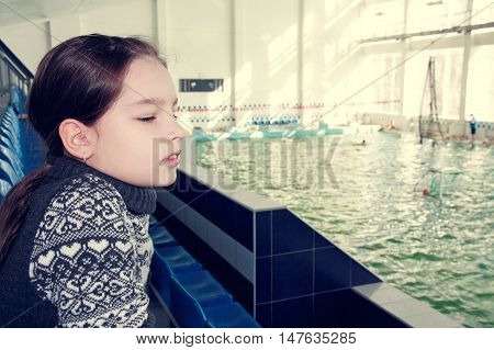 Nine-year girl is watching the competition in the swimming pool.