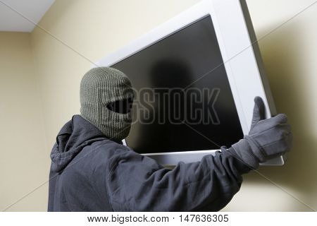 Thief stealing a television from someones house