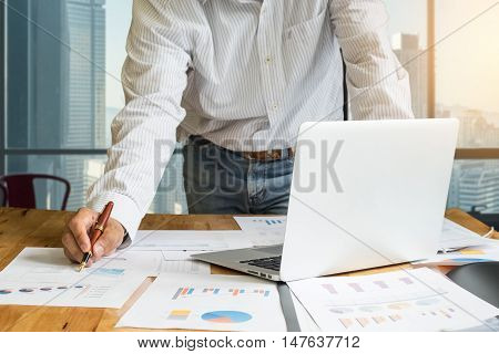 close up of business man hand holding pen for working on laptop computer with business graph information diagram on wooden desk with cityscape background. vintage effect.