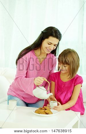 Mother pouring tea into daughters cup in the morning