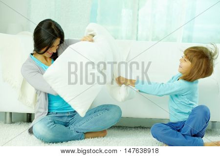 Mother and her little daughter fighting with pillows at home