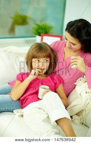 Mother and daughter sitting on sofa and drinking tea with cookies