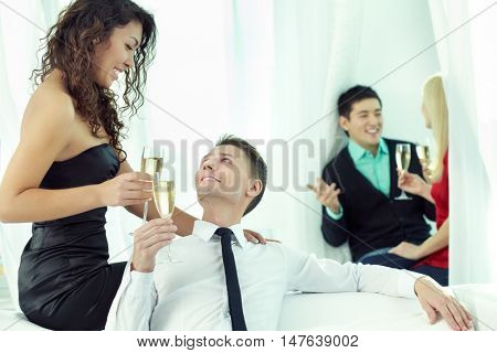 Smiling young people toasting and looking at each other