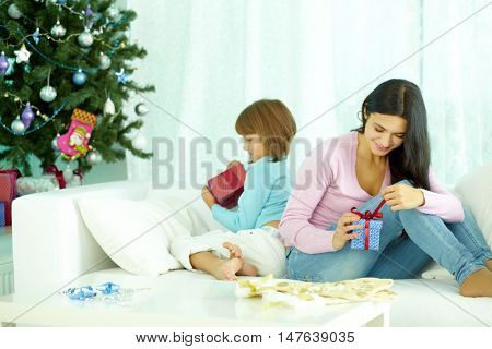 Mother and daughter sitting at Christmas tree and unpacking their presents