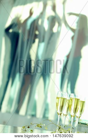 Champagne flute standing at the table with group of people dancing on background