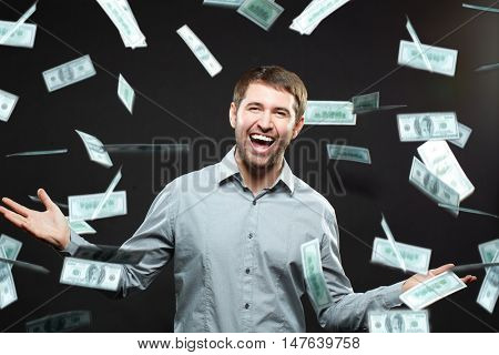 Excited happy successful man standing under money rain against black background