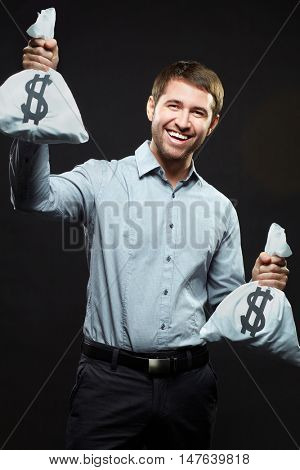 Excited young man holding money bags on black background