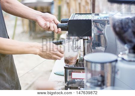 Barista mixing milk and chocolate on espresso machine for making coffee Latte and cappuccino at the coffee machine at the coffee shop
