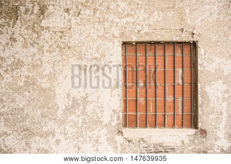 Window closed with bricks in old wall