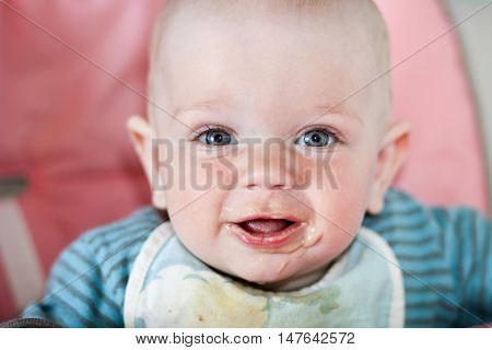 Beautiful baby eats porridge from mom's hand. He is sitting on a pink children's chair