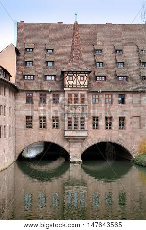 Old red buildings with tower and arch bridge reflected in water. Nuremberg, Germany.