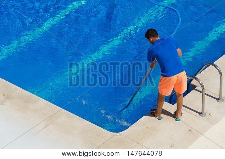 Young Man Cleaning The Swimming Pool